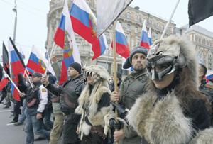 Эти москвичи под трехцветными флагами вышли на демонстрацию 4 ноября, в День народного единства. Составная часть их самоощущения – угнетенность русского человека. Фото Reuters